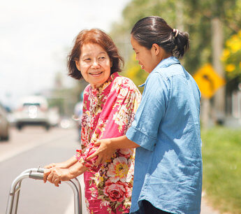 caregiver assisting elderly woman in the road